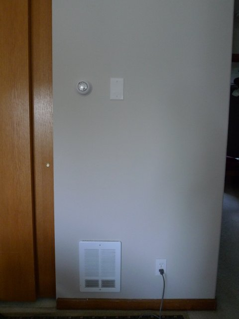Completed installation, showing new thermostat, cover plate, existing heater.